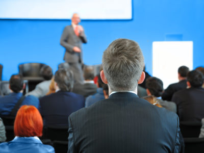 man watching speaker at event - how to plan a corporate event
